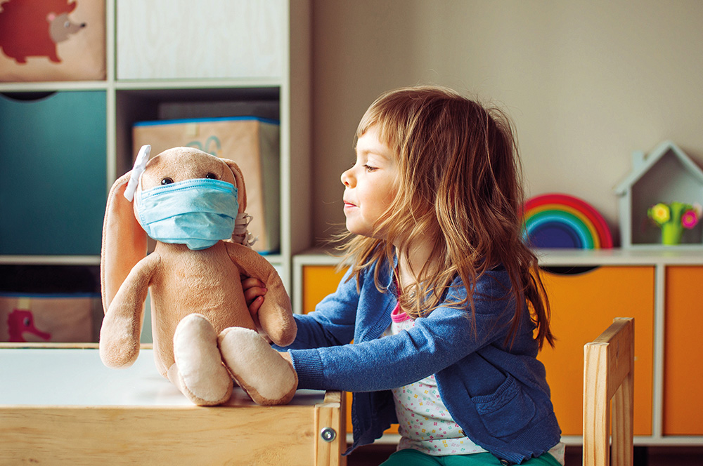 A primary school child playing with a masked teddy bear in a classroom