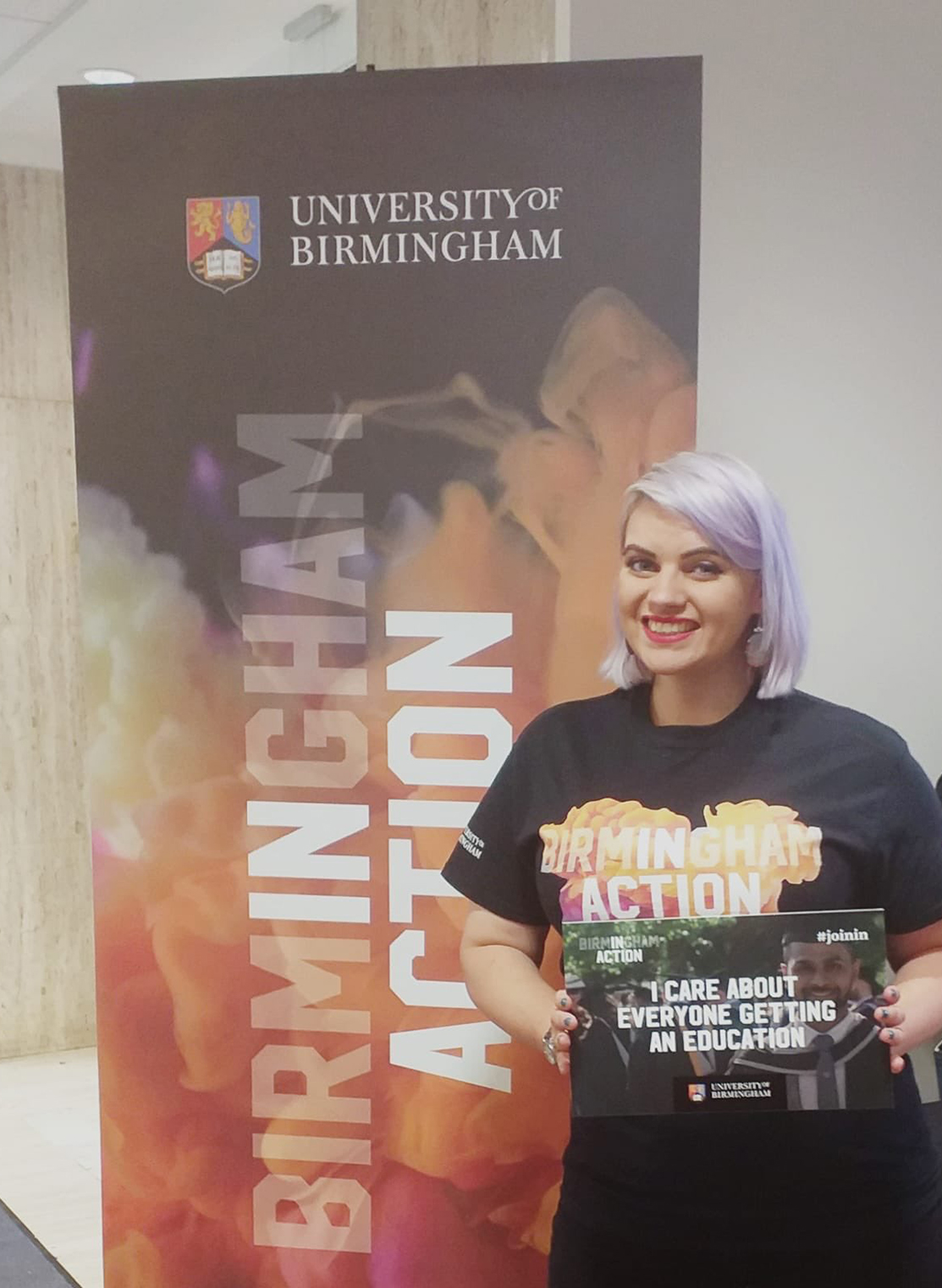 Female wearing black, orange and purple t-shirt that says 'Birmingham In Action' holding a sign that says 'I care about everyone getting an education' in front of a banner that says 'Birmingham In Action.'