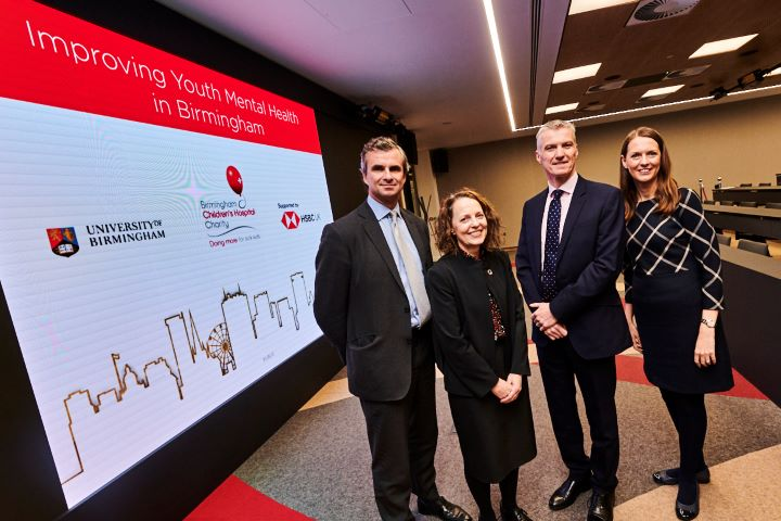 Two men and two women stand in front of a sign with University of Birmingham, HSBC and BCH logos on it