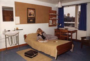 Female student in 1970s suit reading textbook on a bed in Mason Hall. The room includes a sink, mirror, pinboard, desk and shelves
