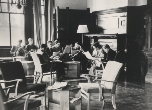 Black and white photo of eight students reading papers sitting in a common room in Manor House in the 1940s