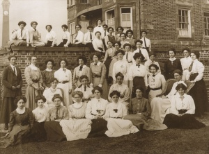 Sepia photo of forty women in Edwardian dress standing outside University House (current day Business School), the first permanent women's halls of residence.