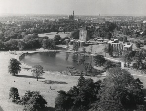 Black and white aerial photo of new halls of residence around the lake at the Vale, with the Birmingham skyline in the distance