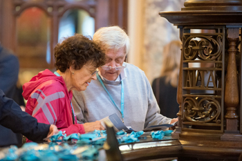 An elderly woman and man looking at name badges