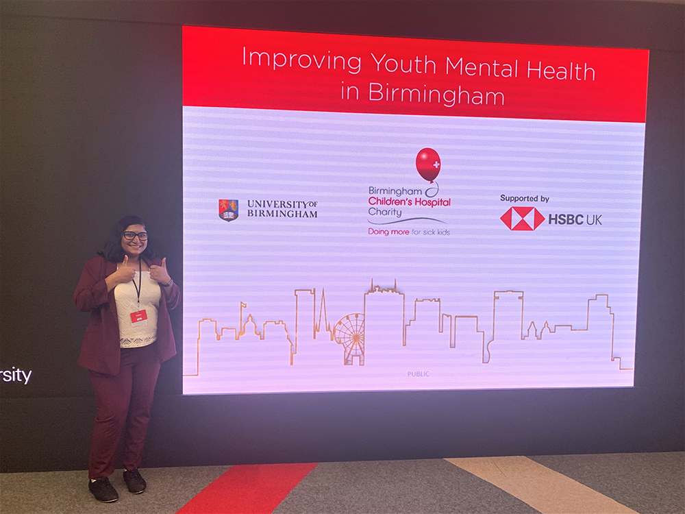 Student stands in front of a sign with University of Birmingham, HSBC and BCH logos on it