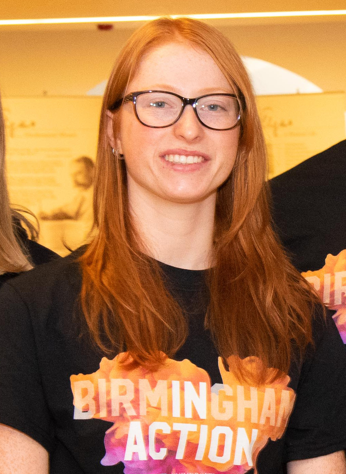 Female student with glasses wearing black and orange t-shirt that says 'Birmingham In Action'