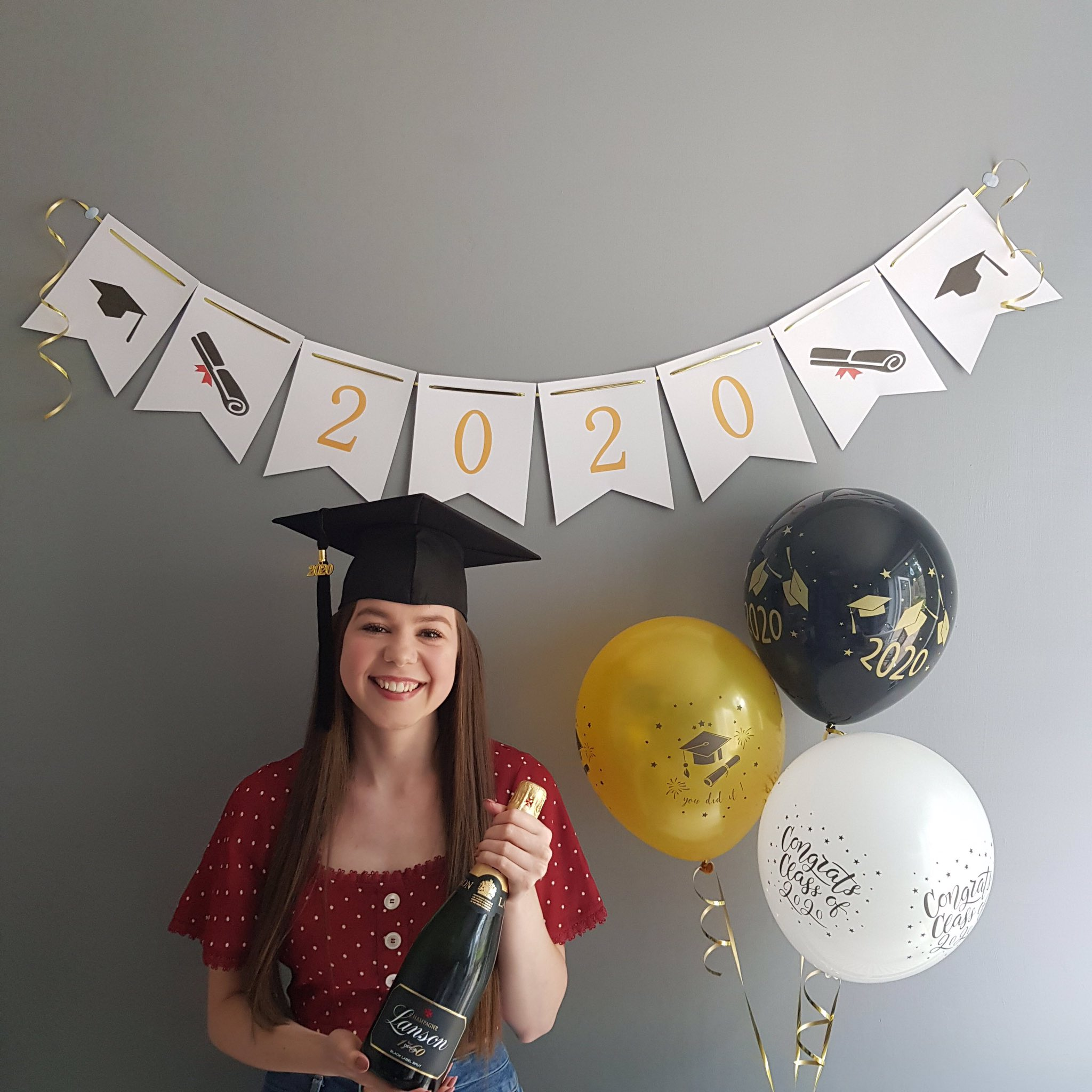 Girl smiling wearing graduation cap with champagne in hand, banner behind her that says 2020 and three balloons next to her