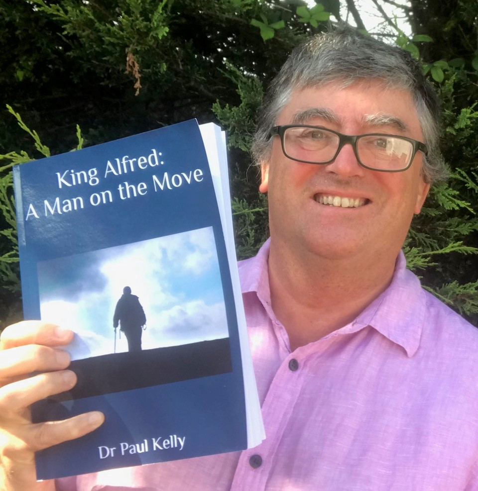 Dr Paul Kelly holding the book he wrote, King Alfred: A Man on the Move