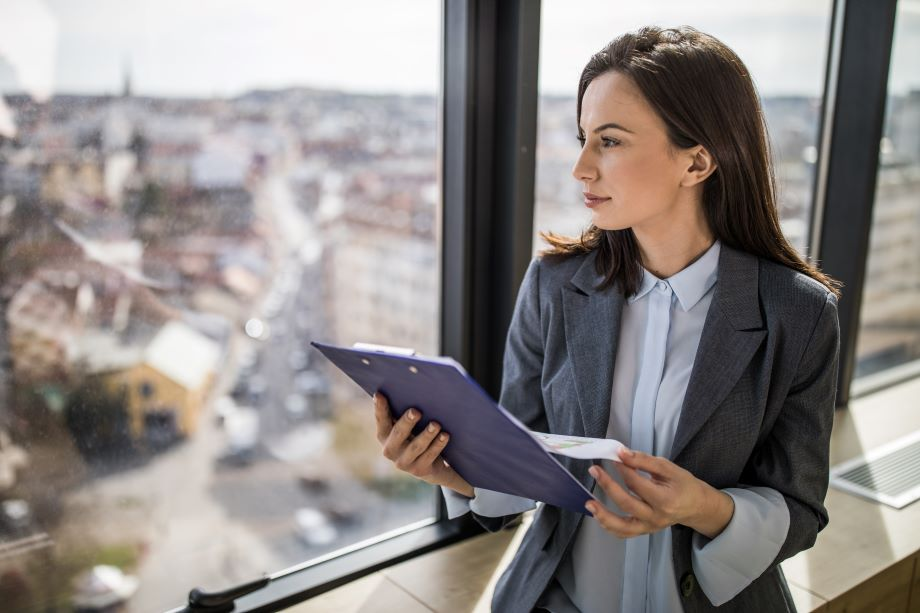 Young female lawyer looks out a window over buildings, while holding a clipboard