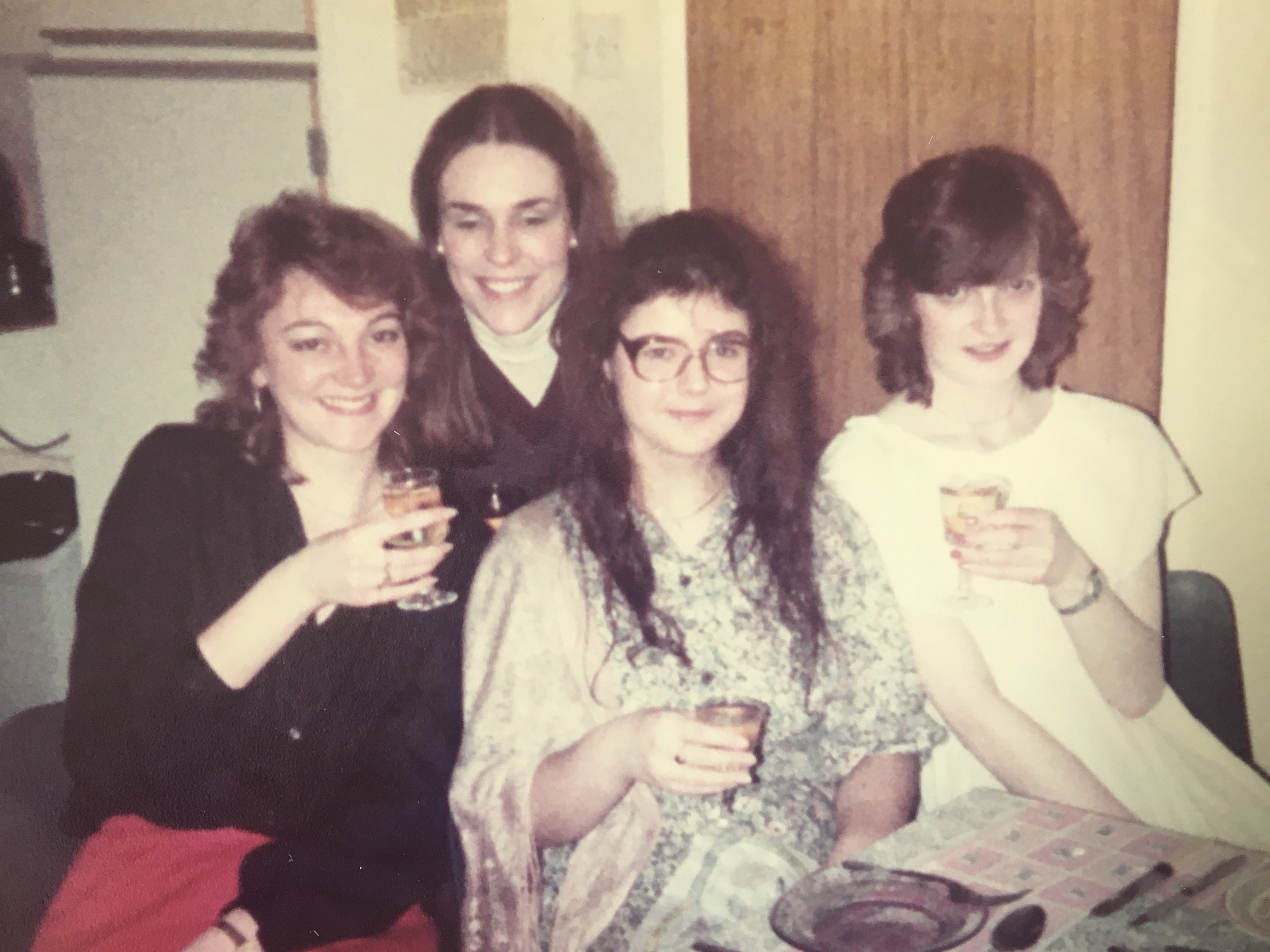 Four friends holding drinks together in the 80's