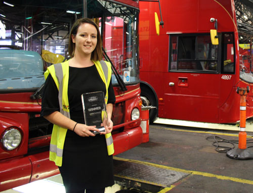Woman in high visibility jacket holding glass trophy, standing in front of red buses