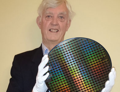 Man holding a disc of silicon chips, wearing white gloves