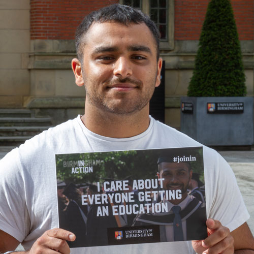 Pav standing outside the Aston Webb Building, holding a board that says I care about everyone getting an education