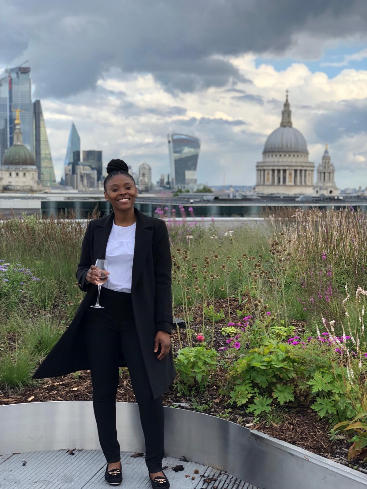 Girl with a champagne glass standing outside behind London skyline