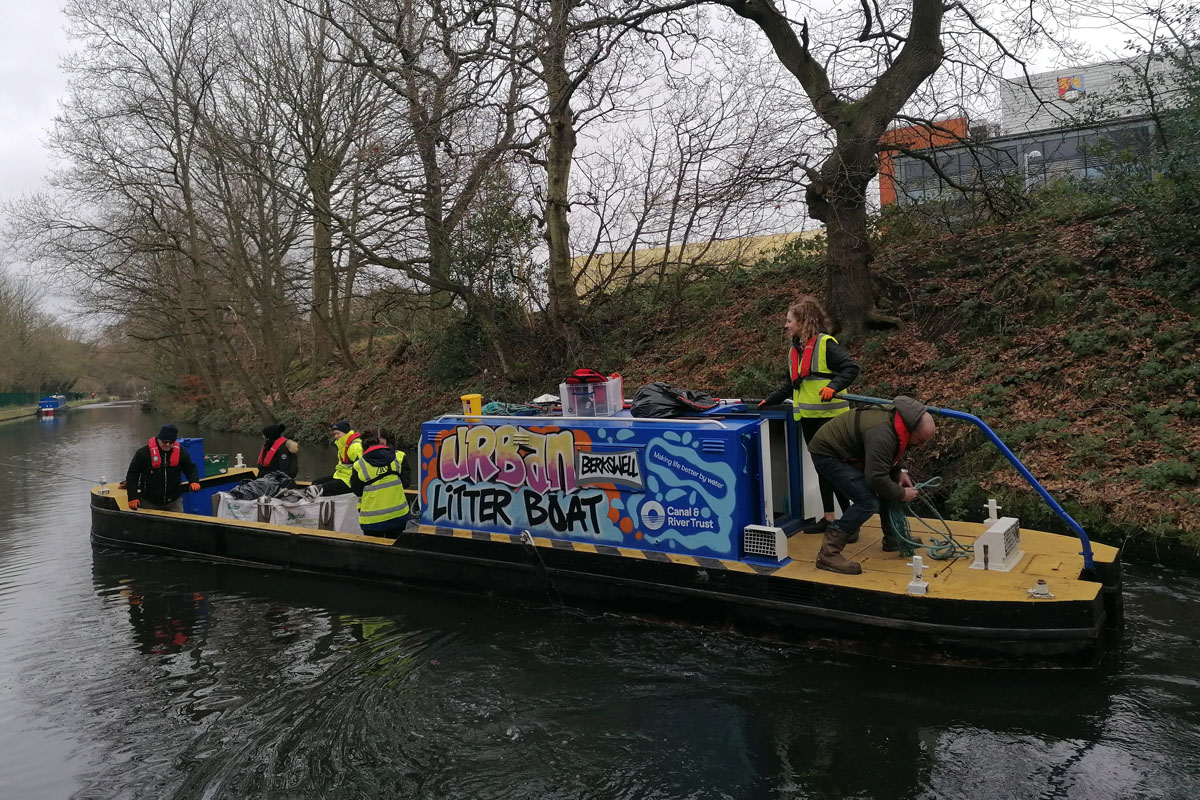 Student volunteers clear waste from canal
